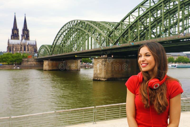 A menina da vida urbana com fones de ouvido e o t-shirt vermelho apreciam seu tempo livre na água de Colônia, Alemanha imagem de stock royalty free