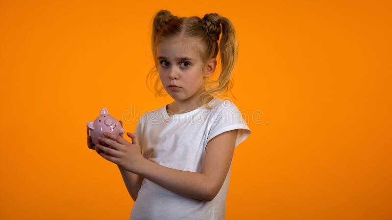 Menina da virada que guarda o piggybank vazio, não tendo nenhum dinheiro, insuficientes economias foto de stock royalty free
