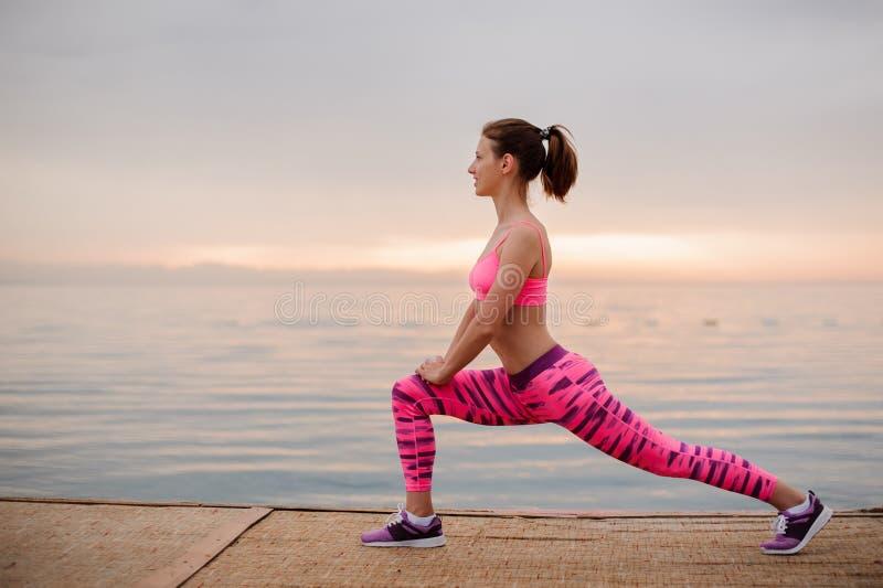 Menina da vista lateral que faz exercícios do estiramento no nascer do sol no beira-mar imagem de stock royalty free