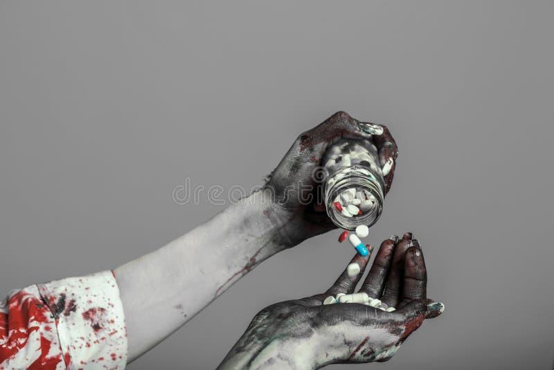 Menina danificada assustador no traje do Dia das Bruxas do nurce que olha como o zombi com os comprimidos no fundo cinzento foto de stock