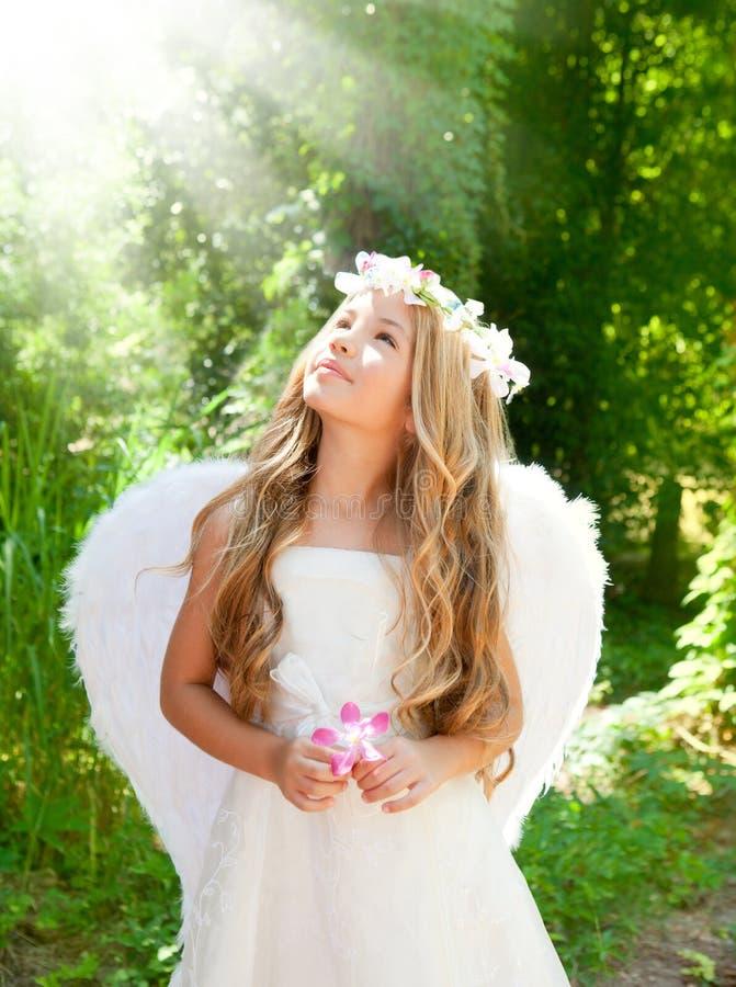 Menina das crianças do anjo na floresta com flor à disposicão imagens de stock royalty free