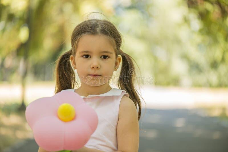 Menina de Adorablr que realiza o balão da forma da flor fora no parque do verão foto de stock royalty free