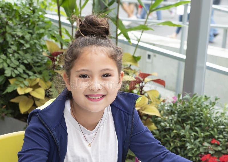 Menina de Amerasian dos anos de idade dez com um sorriso grande em férias em Seattle, Washington foto de stock