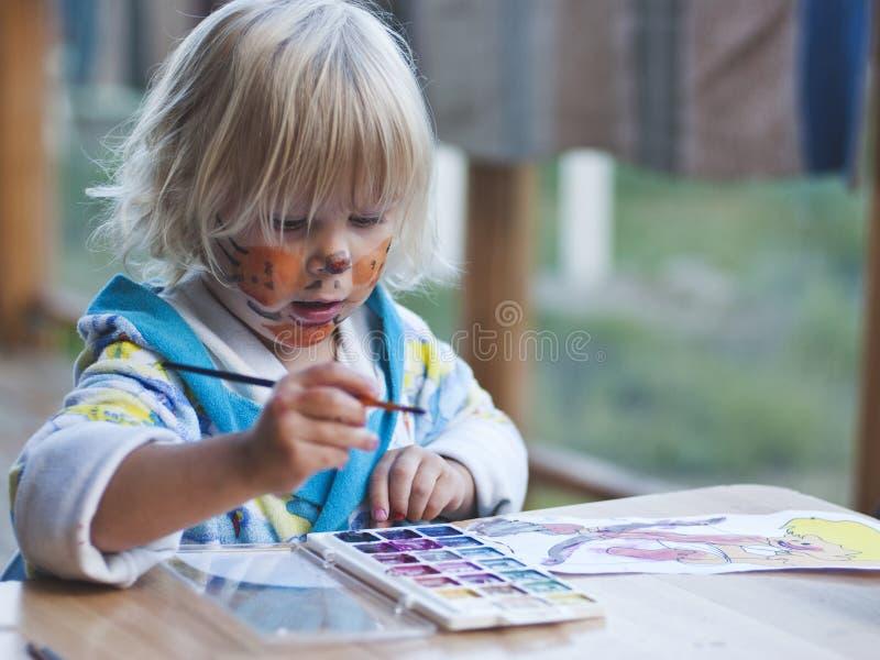 A menina de 3 anos tira pinturas imagem de stock