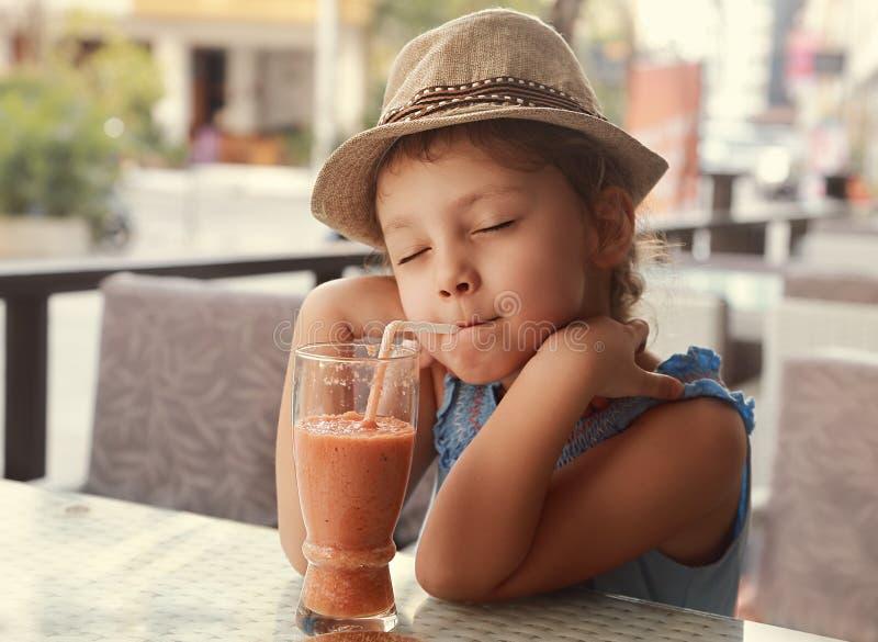 Menina de apreciação feliz da criança que bebe wi naturais saborosos do suco do batido imagens de stock
