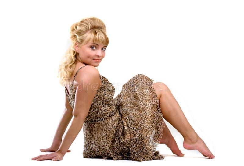 Menina de assento em um vestido do leopardo imagem de stock royalty free