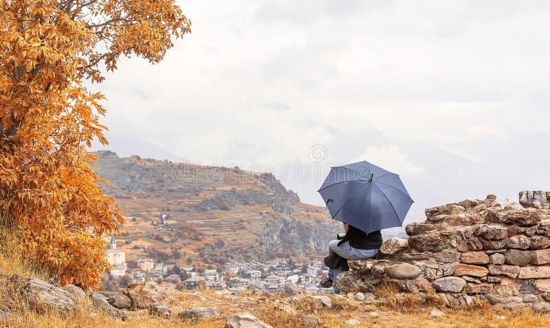 Menina de assento que guarda um guarda-chuva fotografia de stock royalty free