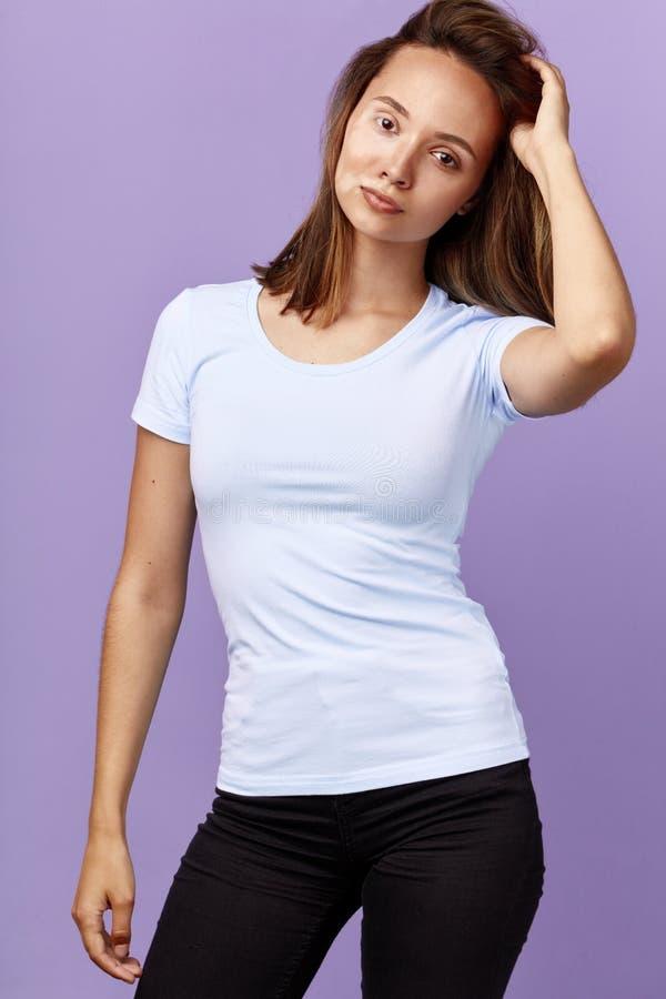 Menina de Attracative no t-shirt e nas calças de brim brancos com o braço aumentado que levanta à câmera foto de stock
