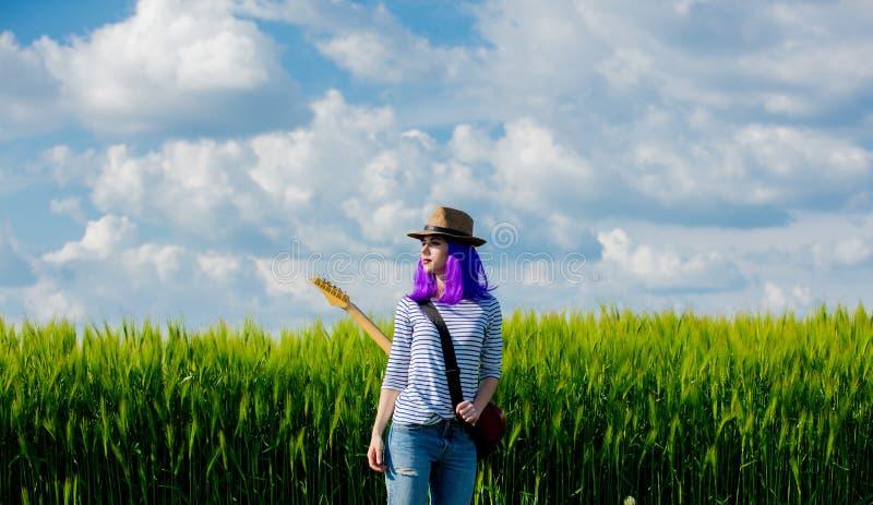 Menina de Beautfiul com a guitarra no campo de trigo foto de stock