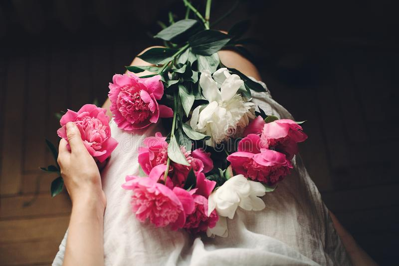 Menina de Boho no vestido branco de Boêmia que guarda peônias cor-de-rosa bonitas nos pés, vista superior Espaço para o texto E imagens de stock royalty free