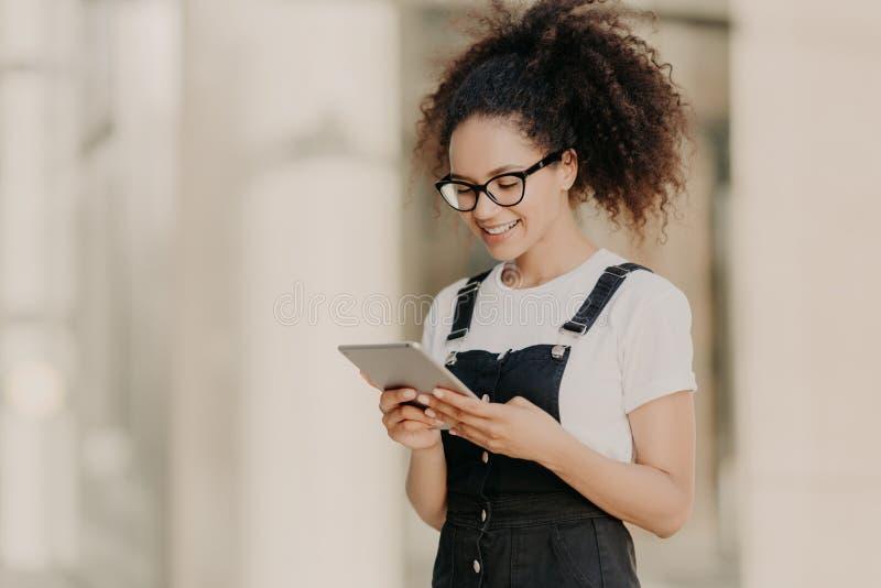 A menina de cabelo encaracolado bonita olha a tela digital da tabuleta com sorriso, lê algum texto ou o livro eletrônico, veste e imagens de stock