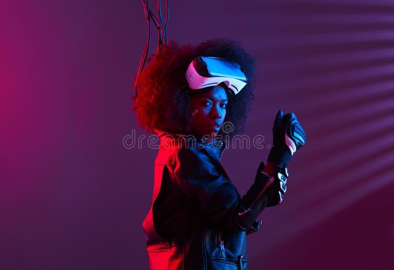 A menina de cabelo escura encaracolado vestida em um casaco de cabedal preto e em luvas est? vestindo os vidros da realidade virt fotografia de stock
