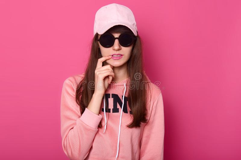 A menina de cabelo escura nova do adolescente que veste o hoodie cor-de-rosa à moda, tampão e subglasses pretos, toca em seu bord imagem de stock