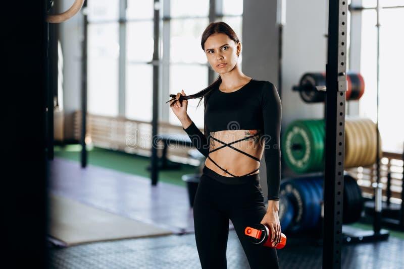Menina de cabelo escuro atlética vestida em suportes pretos do sportswear com água em sua mão perto do equipamento de esporte no  fotos de stock