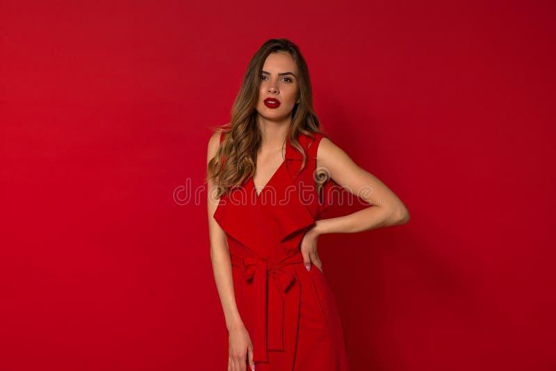 Menina de cabelo escuro elegante lindo, elegante com bordos vermelhos e vestido vermelho Mulher que levanta no fundo isolado foto de stock royalty free