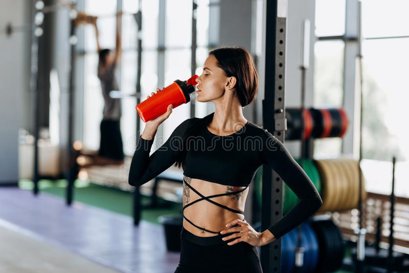 A menina de cabelo escuro magro vestida em bebidas pretas do sportswear molha no gym perto do equipamento de esporte fotos de stock royalty free
