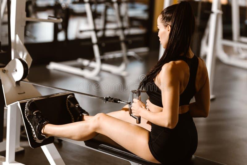A menina de cabelo escuro magro vestida na parte superior e no short pretos dos esportes est? dando certo na m?quina do exerc?cio foto de stock