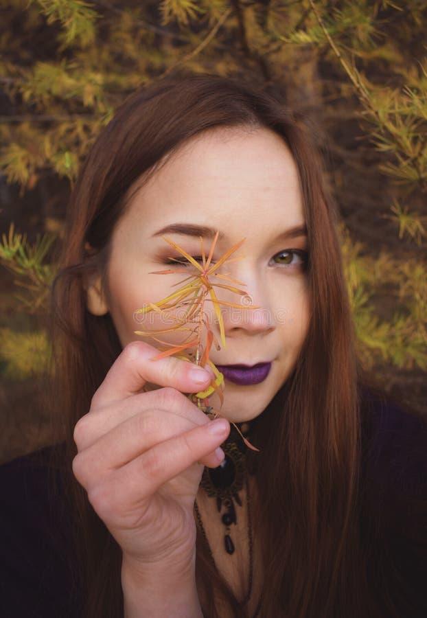 A menina de cabelo escuro no outono guarda uma planta em seus mão e estrabismos imagem de stock