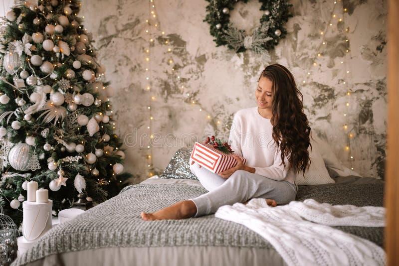 A menina de cabelo escuro vestida na camiseta e nas cal?as brancas guarda um presente do ano novo em suas m?os que sentam-se na c foto de stock