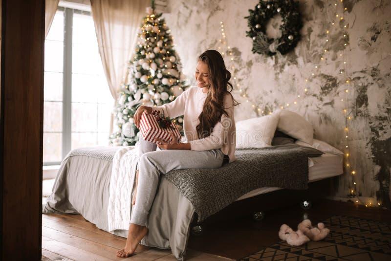 A menina de cabelo escuro vestida na camiseta e nas cal?as brancas guarda um presente do ano novo em suas m?os que sentam-se na c fotos de stock