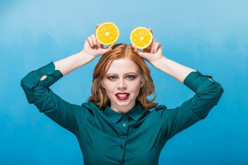 Menina de cabelo vermelha alegre bonita feliz com composição em um fundo azul que sorri com a laranja na cabeça fotografia de stock