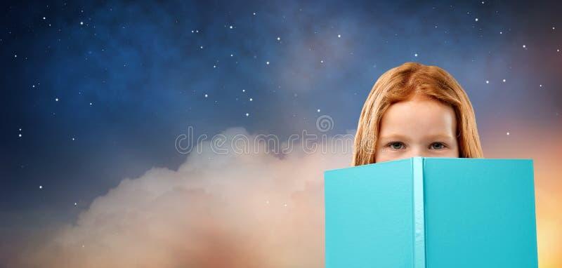 Menina de cabelo vermelha atrás do livro sobre o céu noturno estrelado fotos de stock