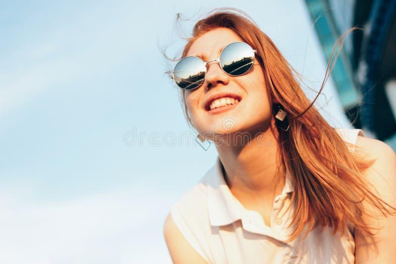 Menina de cabelo vermelha feliz bonita positiva em óculos de sol do espelho no fundo do céu azul, tempo do por do sol do verão fotografia de stock