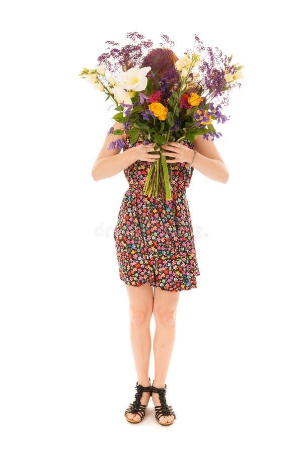 Menina de cabelo vermelha que está com as flores do ramalhete isoladas sobre o whit fotografia de stock