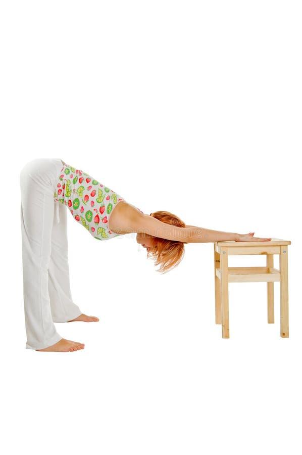 Menina de cabelo vermelha que executa exercícios da aptidão imagens de stock