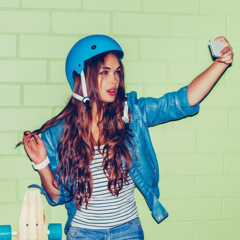 Menina de cabelos compridos bonita com um smartpnone perto de um tijolo verde imagens de stock royalty free