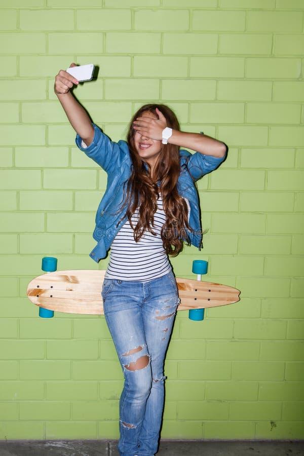 Menina de cabelos compridos bonita com um telefone celular perto de um tijolo verde w fotografia de stock royalty free