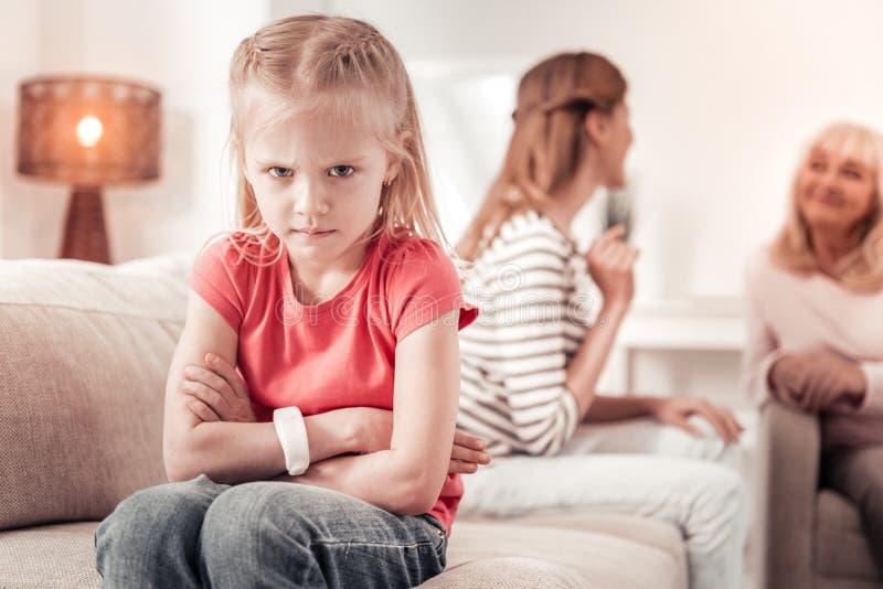 Menina de cabelos compridos bonita em um t-shirt vermelho que olha irritado imagem de stock