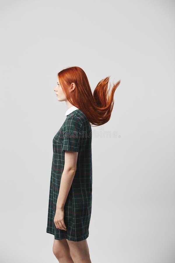 Menina de cabelos compridos do ruivo bonito em um suporte quadriculado verde do vestido no fundo branco no estúdio Seu cabelo é imagem de stock