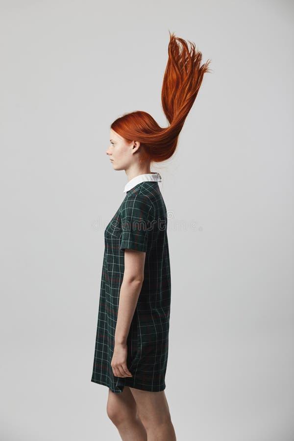 Menina de cabelos compridos do ruivo bonito em um suporte quadriculado verde do vestido no fundo branco no estúdio Seu cabelo é imagem de stock royalty free