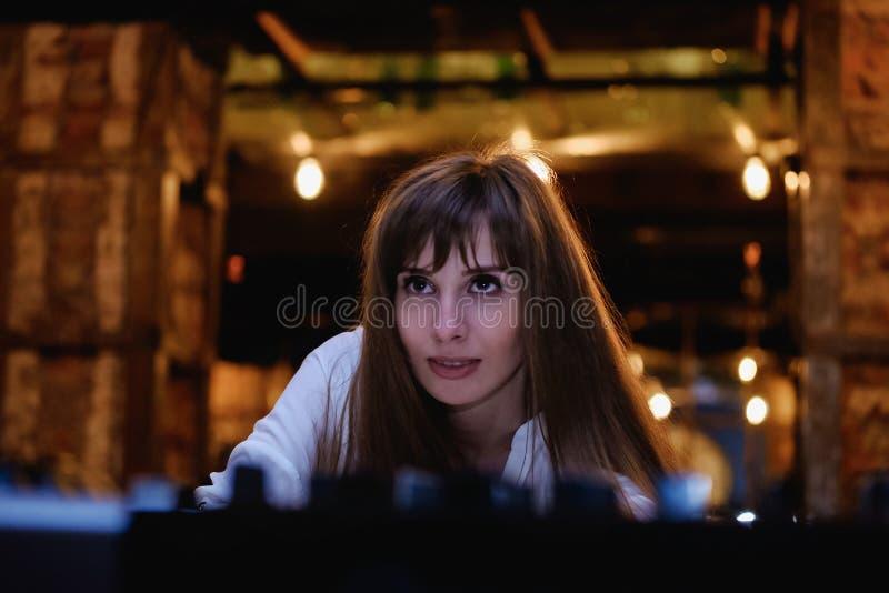 Menina de cabelos compridos em uma blusa branca a menina olha acima, vida noturno, partido imagens de stock