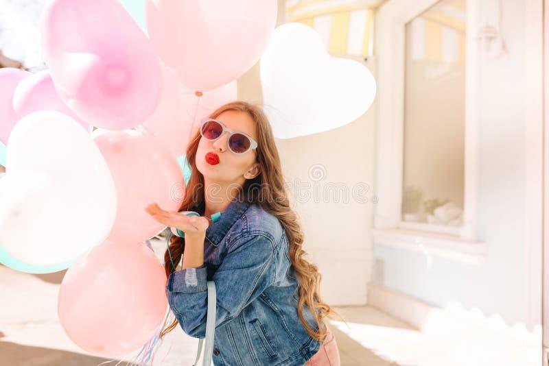 Menina de cabelos compridos de encantamento nos óculos de sol à moda que enviam o beijo ao levantar com balões do coração Jovem m imagem de stock