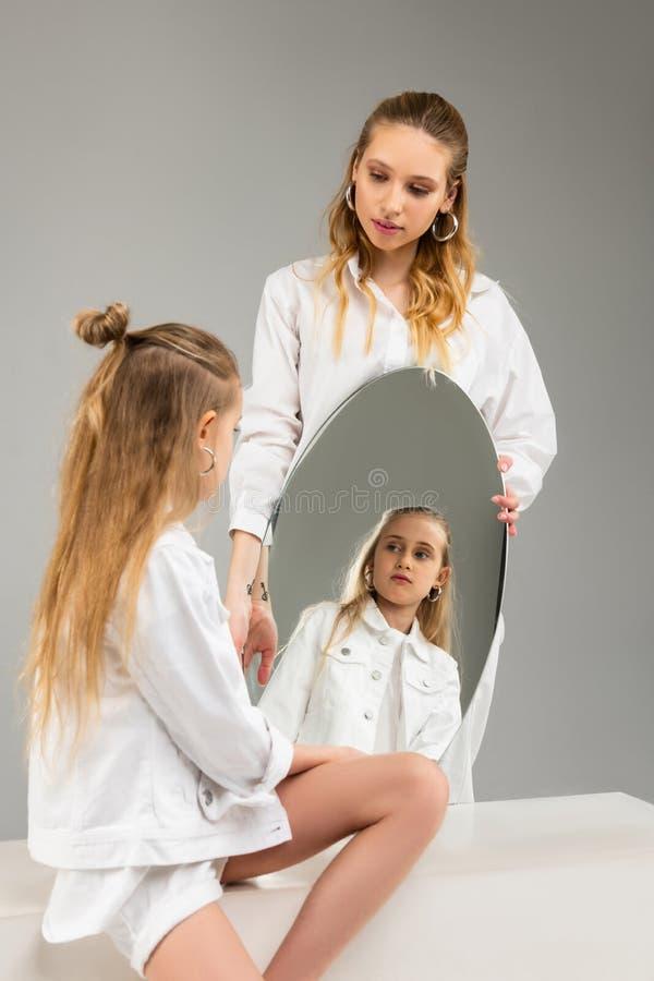 Menina de cabelos compridos na roupa branca que olha seriamente nela que reflete imagens de stock