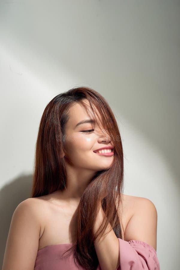 Menina de cabelos compridos rom?ntica no vestido na moda que levanta com sorriso t?mido Foto interna da jovem mulher graciosa no  imagens de stock
