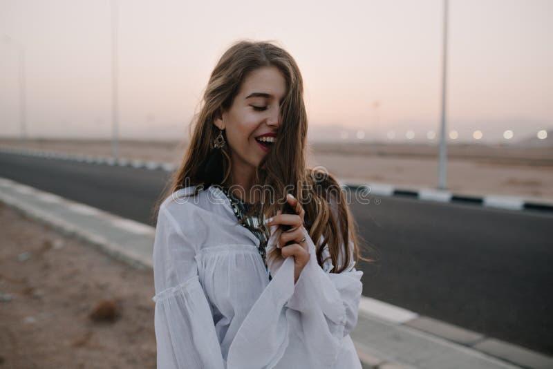 Menina de cabelos compridos de sorriso atrativa que levanta com os olhos fechados ao andar abaixo da estrada na noite do ver?o Re fotografia de stock