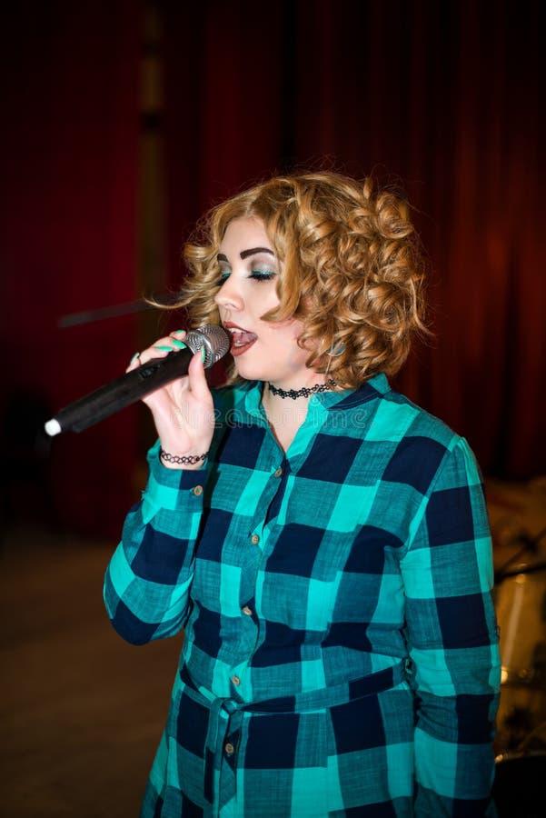 Menina de canto com microfone fotografia de stock