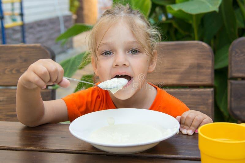 A menina de cinco anos engraçada com prazer come o papa de aveia para o café da manhã fotografia de stock