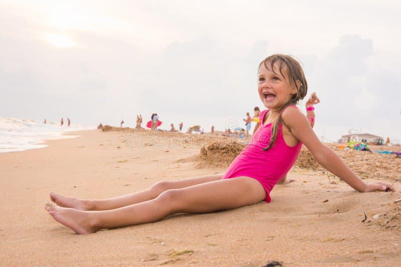 A menina de cinco anos senta-se na praia na costa de mar da noite em um dia nebuloso foto de stock