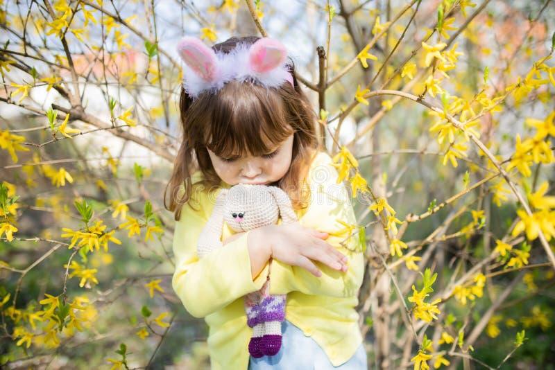 Menina de coelho triste pequena infeliz que guarda o jardim da flor do brinquedo do coelho na primavera fotografia de stock royalty free