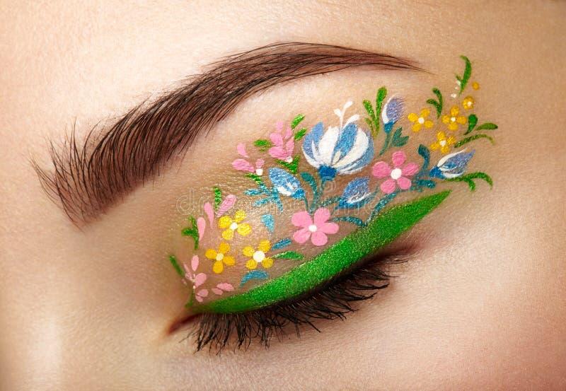 Menina de composição do olho com flores imagens de stock