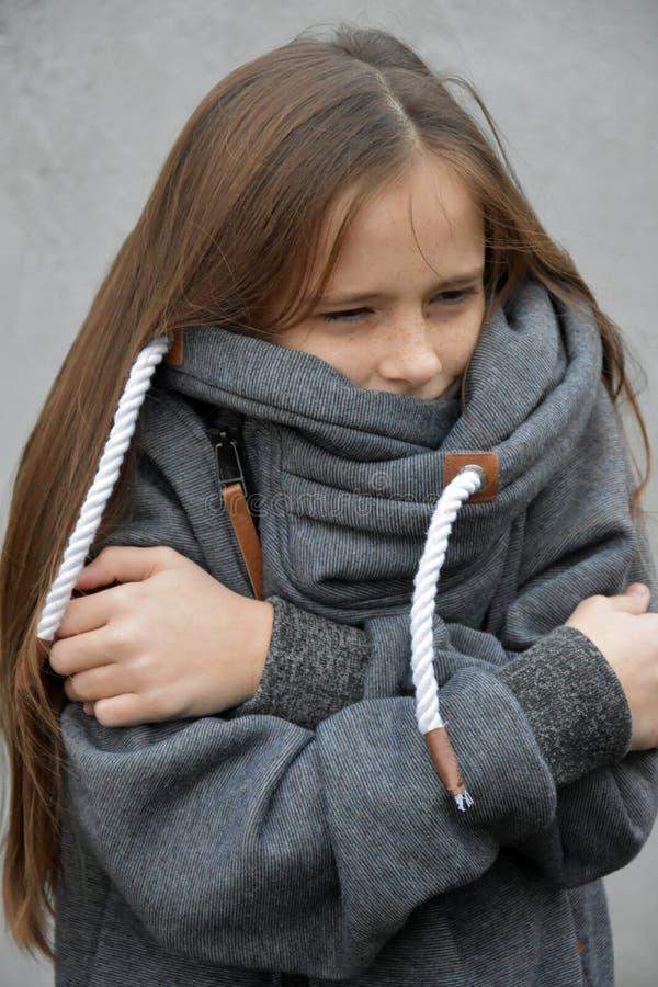 A menina de congelação aconchega-se em sua camiseta de lã imagens de stock royalty free