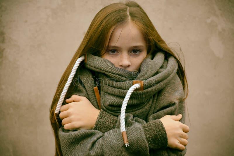 A menina de congelação aconchega-se em sua camiseta de lã fotos de stock royalty free