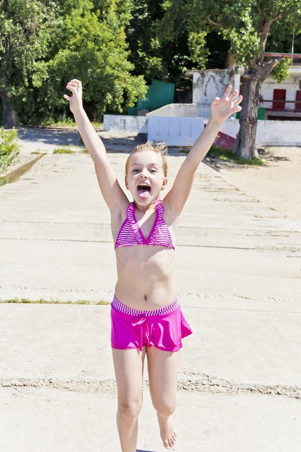 Menina de corrida e gritando no roupa de banho cor-de-rosa fotografia de stock royalty free