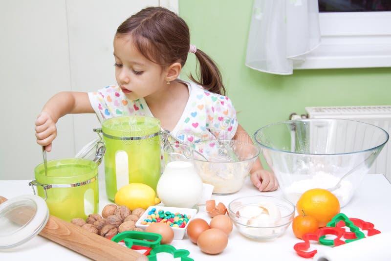 Menina de Cutee que bakeing na cozinha foto de stock royalty free