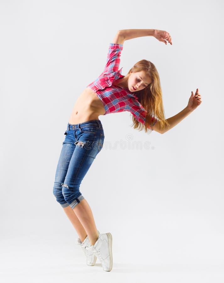 Menina de dança moderna nova nas calças de brim foto de stock