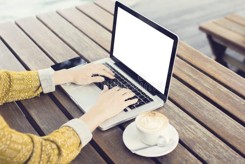 Menina de datilografia com a tela, o smartphone e o copo vazios do portátil do coff imagens de stock